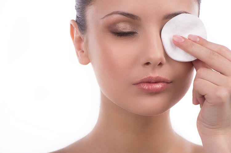 mujer limpiandose la cara con agua micelar